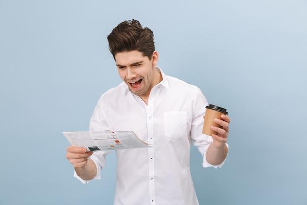 Portrait d'un joyeux beau jeune homme debout isolé sur bleu, tenant une tasse de café à emporter, lisant le journal