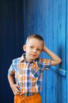 Portrait de joyeux beau petit garçon heureux contre le vieux mur bleu texturé