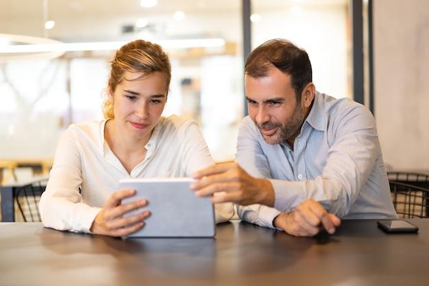 Portrait de joyeux collègues sur une tablette numérique au café