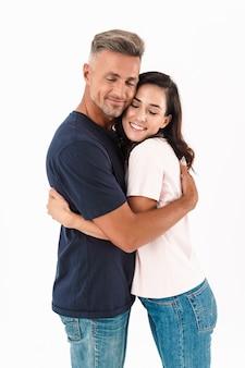 Portrait d'un joyeux couple d'amoureux adultes heureux isolé sur mur blanc.