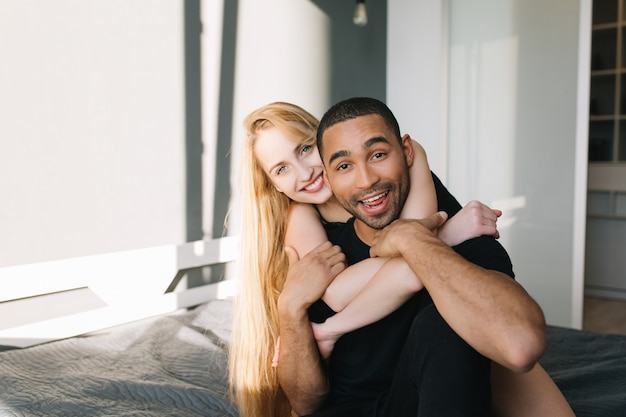 Portrait joyeux couple amoureux de jolie jeune femme aux longs cheveux blonds étreignant beau mec sur le lit. matin ensoleillé à la maison, appartement moderne, s'amuser, romance