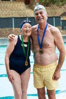 Portrait de joyeux couple de personnes âgées debout au bord de la piscine