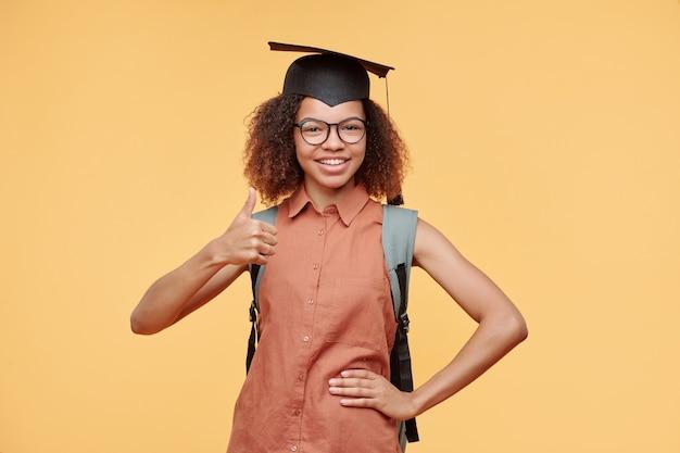 Portrait de joyeux étudiant diplômé noir satisfait en cap montrant le pouce vers le haut comme signe de qualité, fond jaune