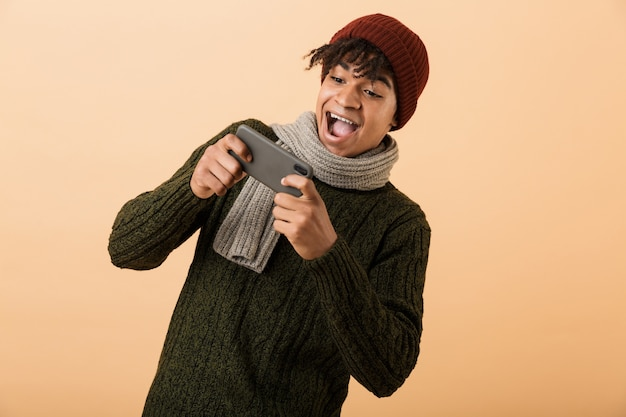 Portrait de joyeux garçon afro-américain gamer portant chapeau et écharpe à jouer à des jeux vidéo sur smartphone, isolé sur fond jaune