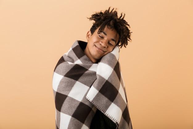 Portrait de joyeux garçon afro-américain souriant tout en couvrant en couverture, isolé sur mur beige
