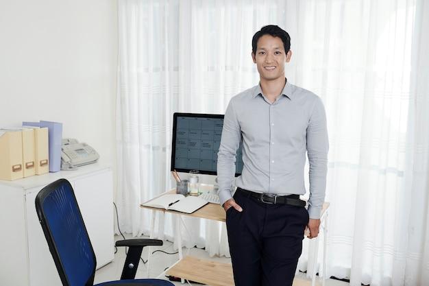 Portrait de joyeux jeune entrepreneur debout à son bureau à domicile avec calendrier sur écran d'ordinateur