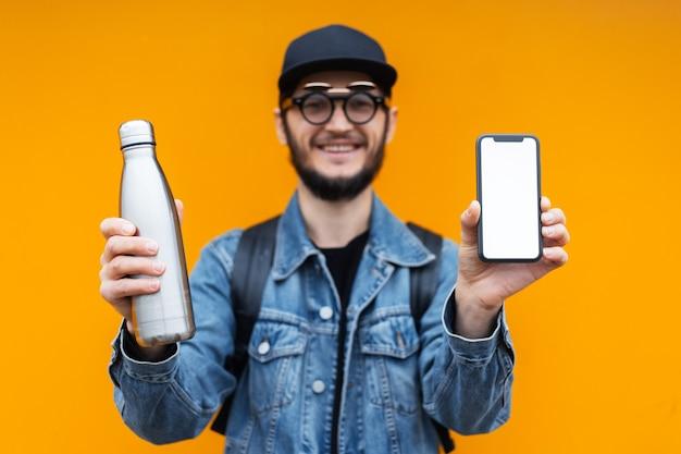 Portrait de joyeux jeune hipster, tenant une bouteille en acier thermo eco pour l'eau et smartphone avec maquette blanche, sur un mur jaune ou orange.