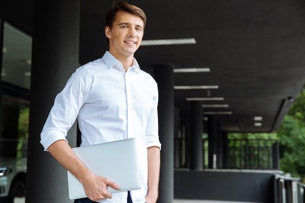 Portrait de joyeux jeune homme d'affaires près du centre d'affaires