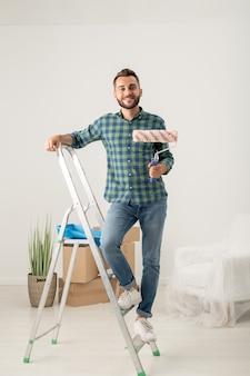 Portrait de joyeux jeune homme barbu debout avec rouleau à peinture sur escabeau dans un nouvel appartement avec des trucs en mouvement