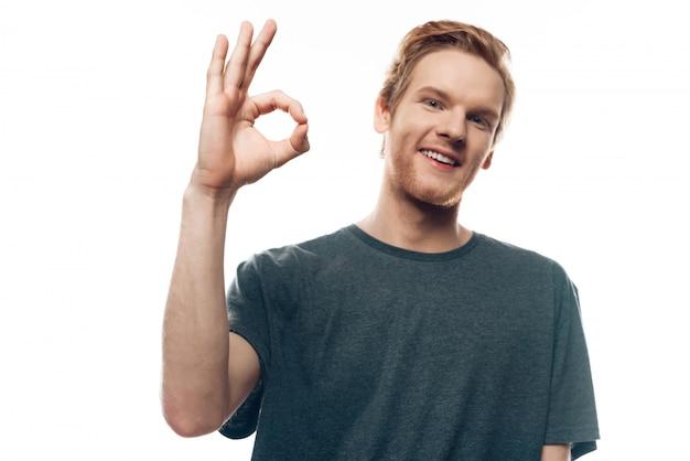 Portrait de joyeux jeune homme montrant le geste correct