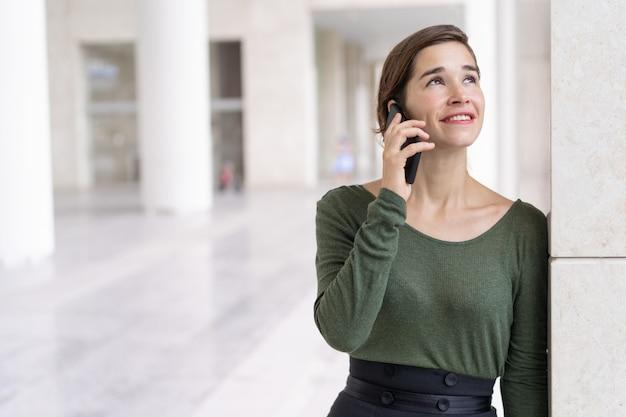 Portrait de joyeux jeune manager ou étudiant parlant au téléphone