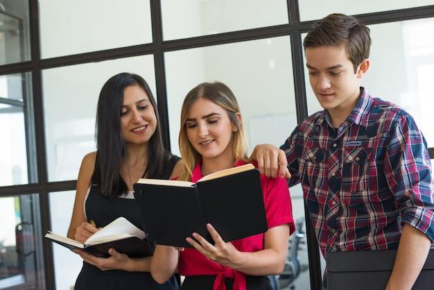 Portrait de joyeux jeunes étudiants partageant leurs devoirs au collège