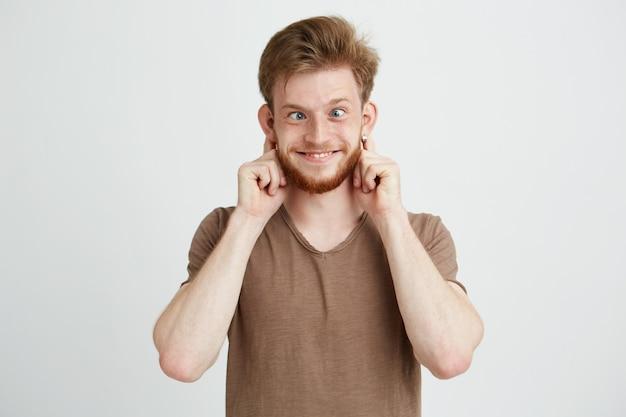 Portrait de joyeux joyeux jeune homme faisant une grimace drôle.