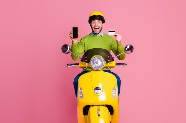 Portrait de joyeux mec gai équitation cyclomoteur tenant dans les mains carte bancaire cellulaire