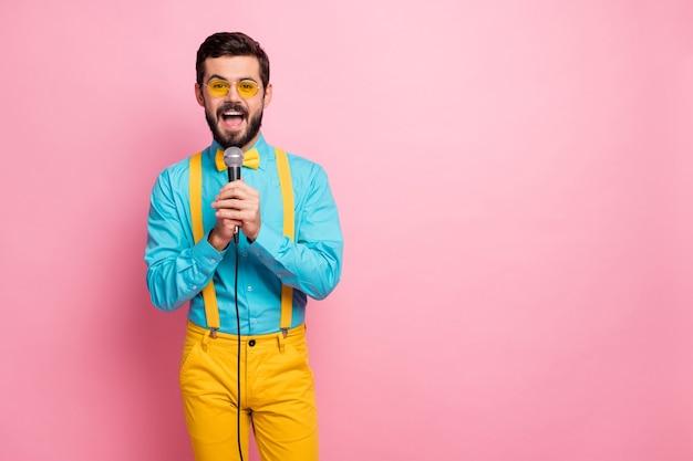 Portrait de joyeux mec heureux tenir microphone chanter karaoké