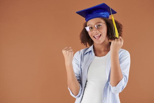 Portrait de joyeux métis diplômé du secondaire en casquette académique debout sur fond isolé et faisant un geste oui