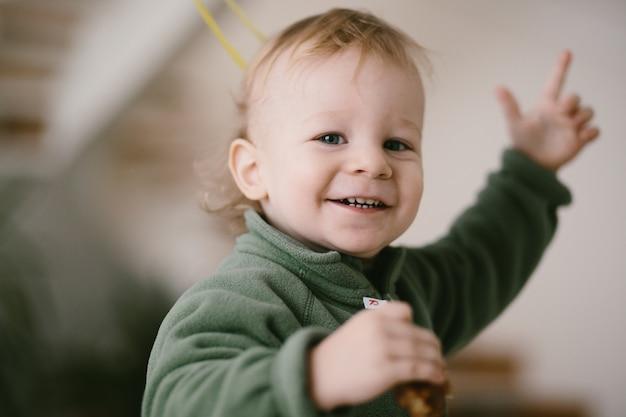 Portrait d'un joyeux petit enfant dans des cavaliers verts