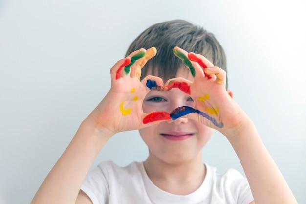 Portrait de joyeux petit garçon d'âge préscolaire mignon 5-6 ans avec des mains peintes colorées. mains souriantes. dessin au doigt, éducation et développement de l'enfant. enfance heureuse.