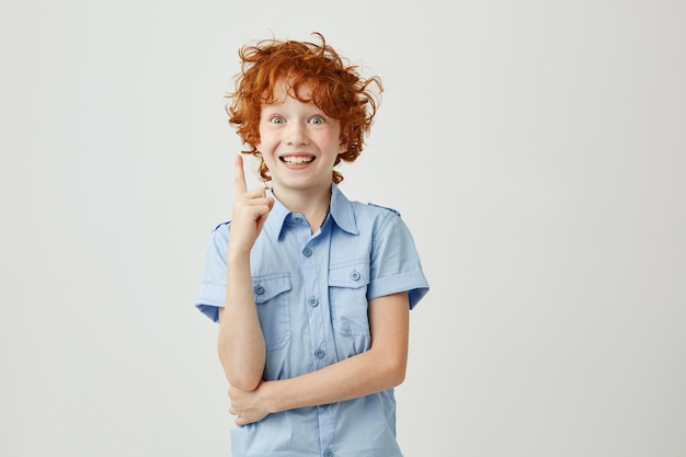 Portrait de joyeux petit garçon aux cheveux roux et taches de rousseur souriant, pointant à l'envers avec le doigt, ayant une expression folle. copiez l'espace.