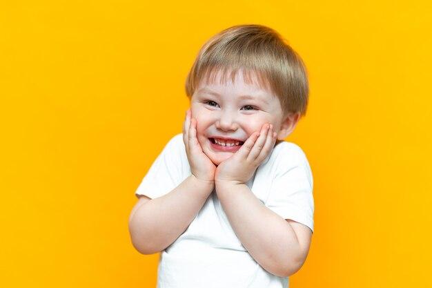 Portrait de joyeux petit garçon enfant de trois ans, debout isolé sur fond jaune. regardant la caméra. montrant des dents blanches, souriant