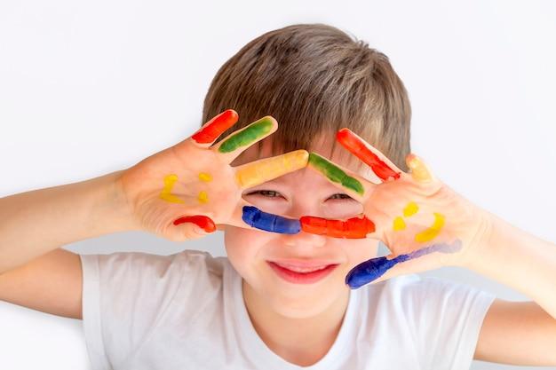 Portrait de joyeux petit garçon mignon avec les mains peintes colorées