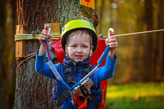 Portrait de joyeux petit garçon s'amusant dans le parc aventure souriant à la caméra portant un casque et des équipements de sécurité.