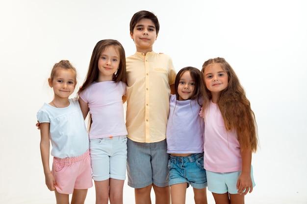 Le portrait de joyeux petits enfants mignons garçon et filles dans des vêtements décontractés élégants regardant la caméra contre le mur blanc