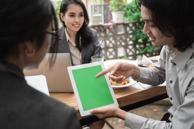 Portrait joyeux de la réunion de l'équipe de jeunes entreprises asiatiques dans un café montrant l'espace de copie en tablette