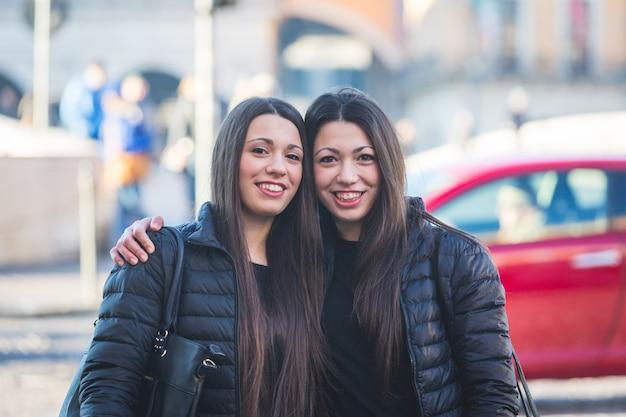 Portrait de jumeaux dans la ville avec la circulation