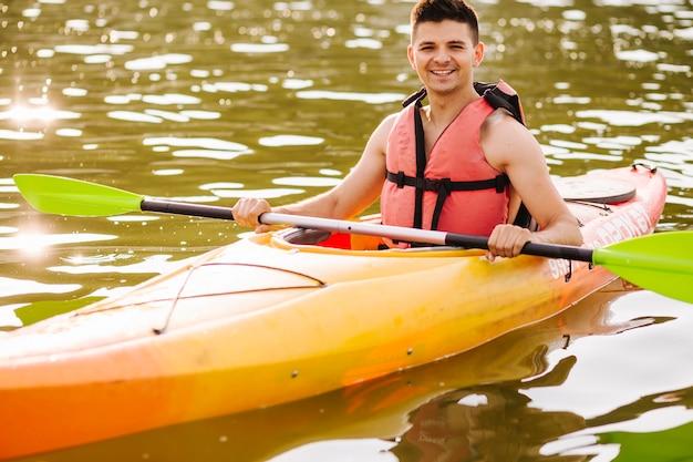 Portrait de kayakiste mâle sur la surface de l'eau ondulée brillante