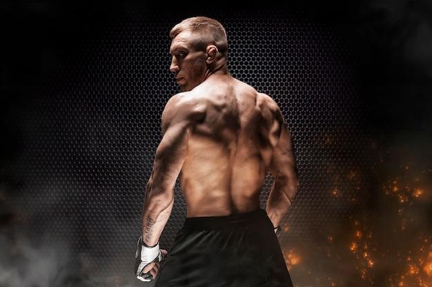 Portrait de kickboxer sur fond de grille en acier. vue arrière. le concept de sports et d'arts martiaux mixtes. technique mixte