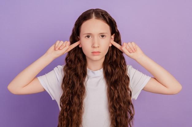 Portrait de kid girl fermer les oreilles doigts isolés sur fond violet