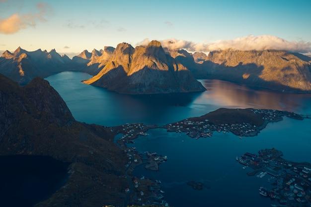 Portrait d'un lac sur un sommet entouré de montagnes rocheuses couvertes de nuages blancs