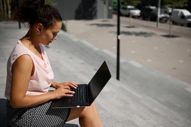 Portrait latéral d'une femme indépendante occupée, d'une start-up, d'un employé de bureau utilisant un ordinateur portable assis sur des marches pendant la pause-café. employé de bureau sur la pause déjeuner en milieu urbain