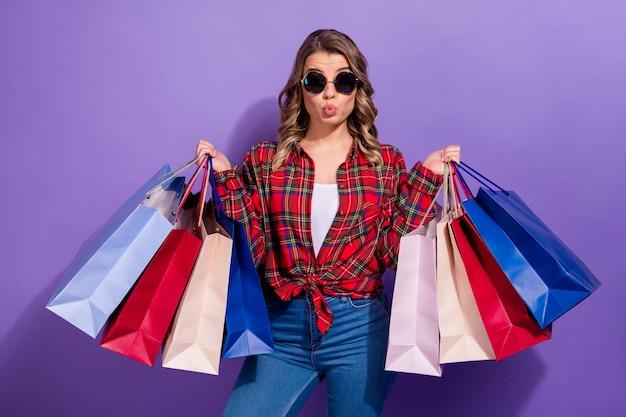 Portrait de lèvres de moue de fille charmante à la mode portent des sacs à provisions
