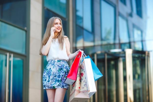 Portrait lifestyle jeune fille blonde, avec des sacs à provisions sortant du magasin.