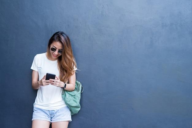 Portrait lifestyle en plein air de jolie jeune fille asiatique sexy dans le style de voyage et de lunettes sur mur gris