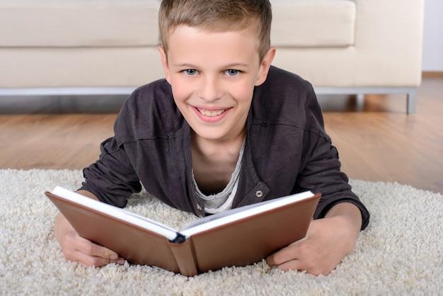 Portrait de livre de lecture garçon intelligent en position couchée sur le sol.