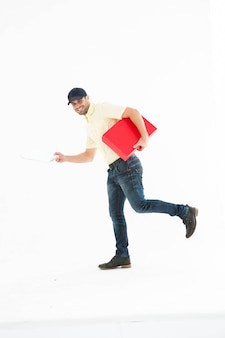 Portrait de livreur confiant avec boîte rouge en cours d'exécution sur fond blanc