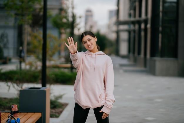Portrait ludique de jolie jeune femme s'amusant dans la rue