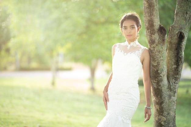 Portrait avec lumière naturelle d'une mariée asiatique en robe de mariée