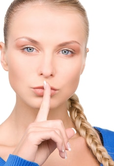 Portrait lumineux d'une adolescente avec le doigt sur les lèvres