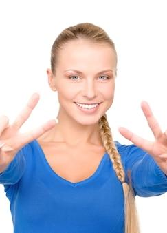 Portrait lumineux de belle blonde montrant le signe de la victoire