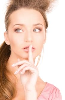 Portrait lumineux de jeune femme avec le doigt sur les lèvres