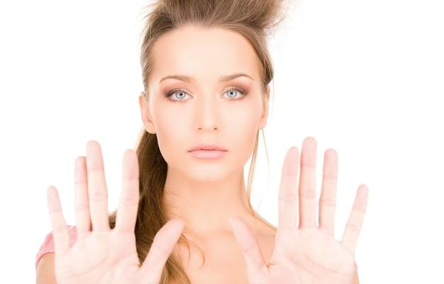 Portrait lumineux de jeune femme faisant un geste d'arrêt
