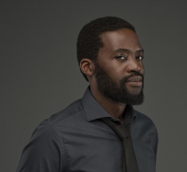 Portrait de ma belle barbu d'âge moyen. un homme afro vêtu d'une chemise de couleur charbon et d'une cravate noire regarde le spectateur par un regard pensif et délicat.