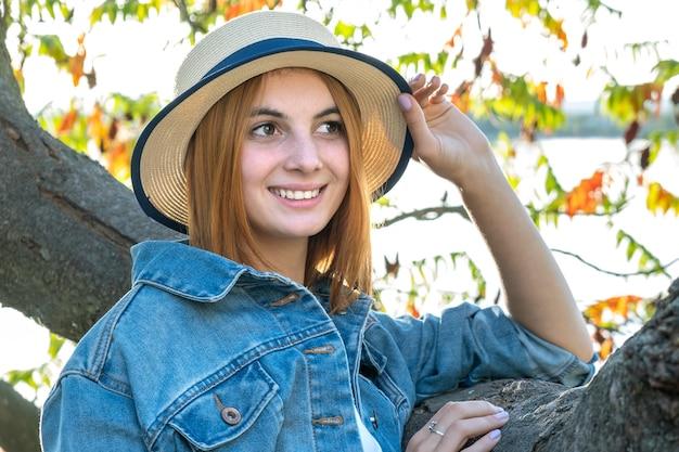 Portrait d'une magnifique adolescente souriante au chapeau jaune et aux cheveux rouges portant une veste en jean à l'extérieur