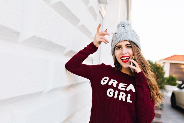 Portrait magnifique aux cheveux longs en bonnet tricoté parlant au téléphone sur un mur gris sur la rue. elle a l'air étonnée.