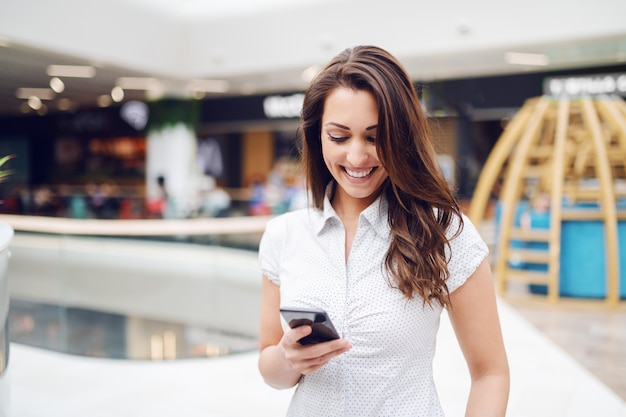 Portrait de magnifique brune souriante en chemise à l'aide de téléphone intelligent dans le centre commercial.