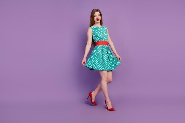 Portrait d'une magnifique dame à pied tenir une jupe courte porter une mini robe à talons hauts sur fond violet